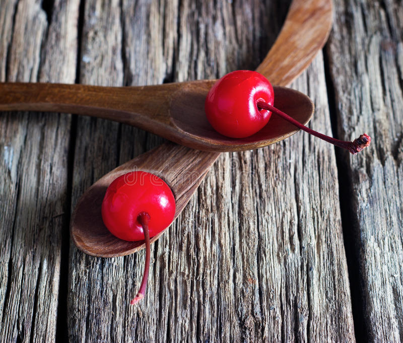 Maraschinokörsbär som är vibrerande på träskeden och gammal tabellbakgrund arkivfoton