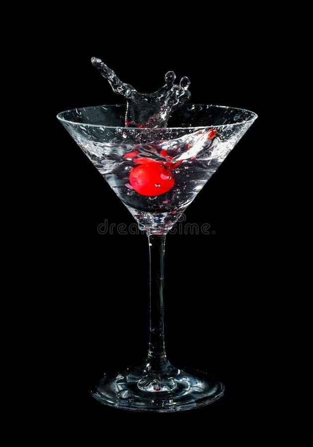 Maraschinokirsche fallen gelassen in Cocktailglas stockbilder