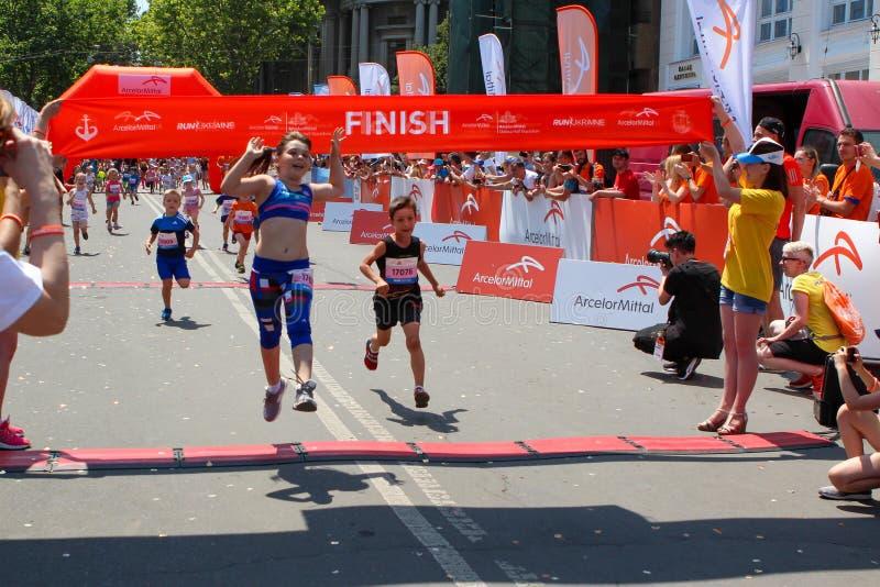 Marathon avec des enfants Badinez les coureurs à la ligne d'arrivée au maraton d'été image libre de droits