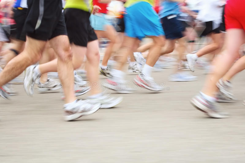 Marathon (in camera motion blur). A motion blur of runners legs in a marathon race royalty free stock image