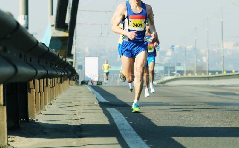Marathon die in het ochtendlicht lopen Het lopen op stadsweg De voeten van de atletenagent het lopen De jonge agenten die op stad stock foto's