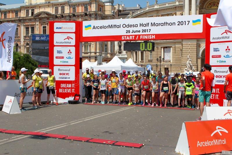 Marathon mit Kindern Scherzen Sie Läufer an Anfangszeile an Sommer maraton lizenzfreies stockfoto