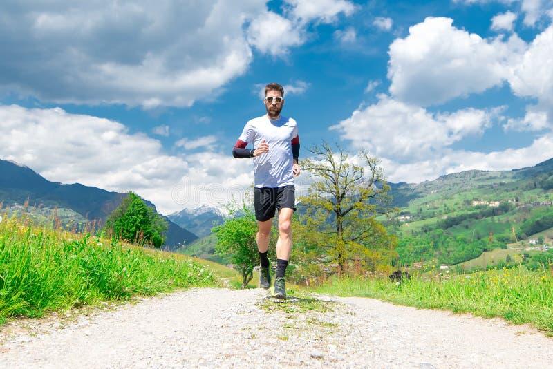 Marathon runner trains in a mountain dirt road stock photo