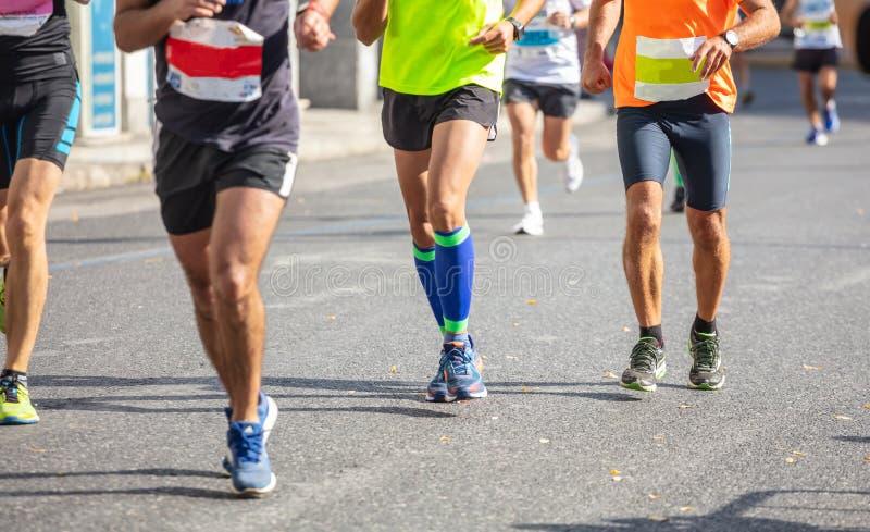 Marathon running race, runners running on city roads, detail on legs stock photography