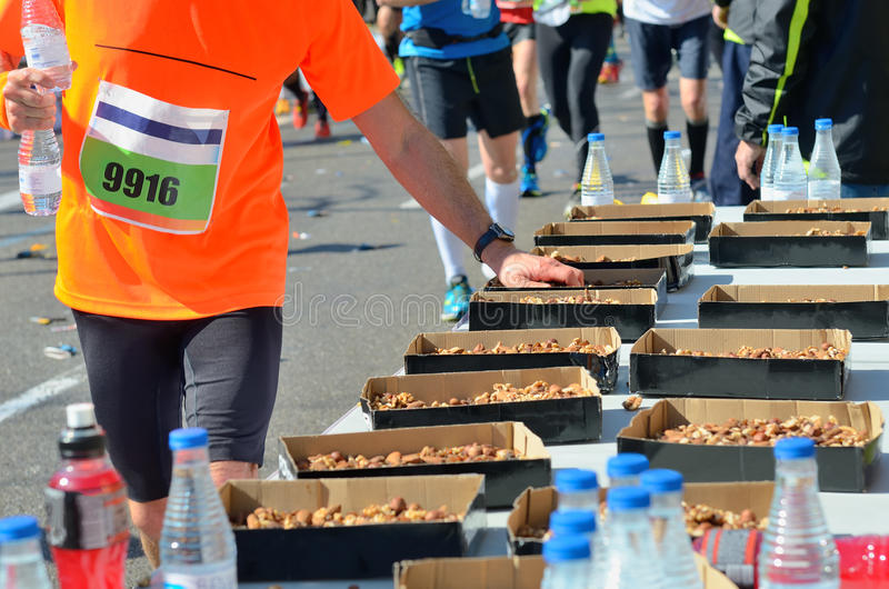 Marathon running road race, runners hand taking food and drinks on refreshment point, sport, fitness and healthy lifestyle royalty free stock photo