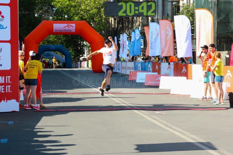 Marathonatleet bij afwerking De gelukkige marathonagent beëindigt lijn stock fotografie