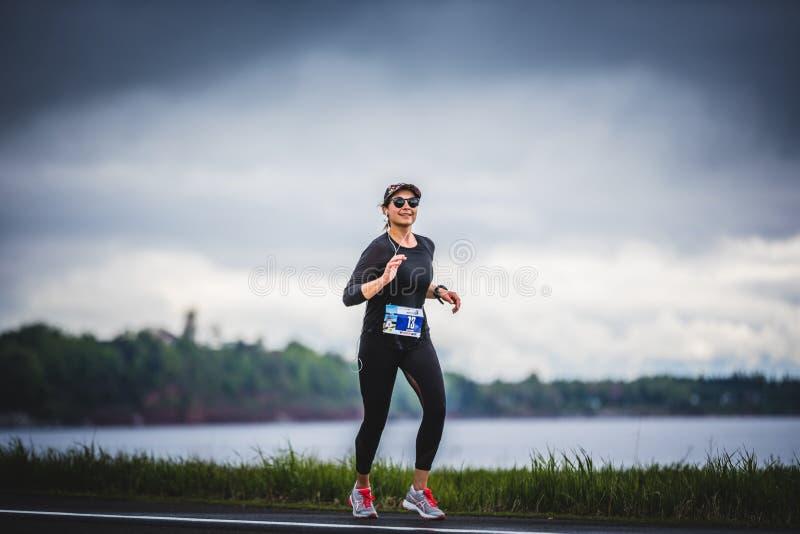 Marathoner aproximadamente los 7km de la mujer joven de la distancia solamente en el Sid fotos de archivo