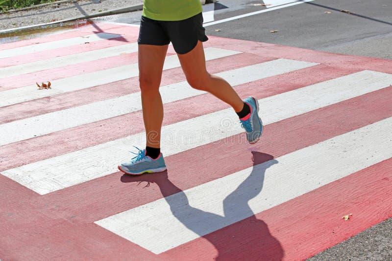 Marathoner läuft schnell über den Fußgängerübergang in der Stadt lizenzfreies stockfoto