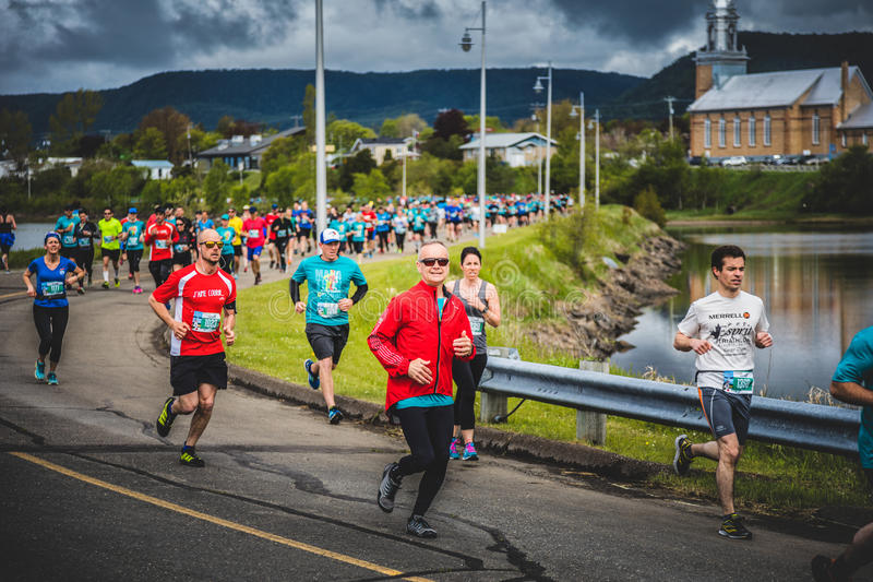 Marathoners in both sides of the street in a little city with ch. CARLETON, CANADA - June 4, 2017. During the 5th Marathon of Carleton in Quebec, Canada stock photo