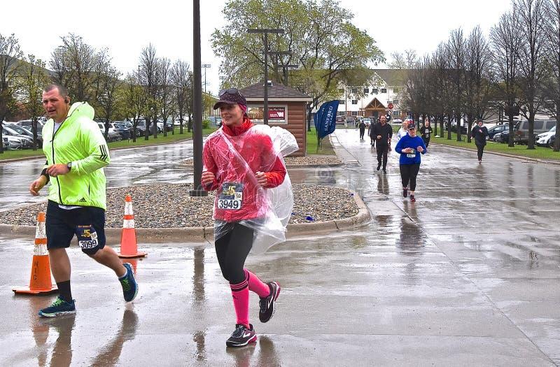 Marathoners compete in Fargo Marathoner in inclement weather. FARGO, NORTH DAKOTA-May 17,  2019 : Marathoners run in inclement weather at the annual Sanford stock images