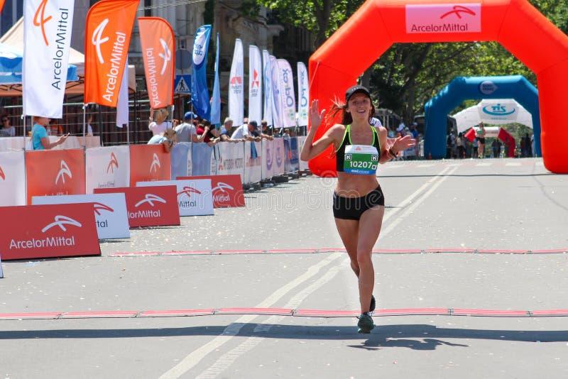 Maratonkvinna på fullföljande Lycklig mållinje för maratonlöpare royaltyfri foto