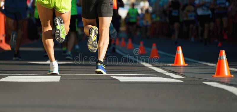 Maratonlöpare som kör på stadsvägen, detalj på ben royaltyfri bild