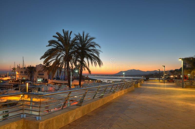 Marbella hamn och klippa på solnedgången royaltyfri fotografi