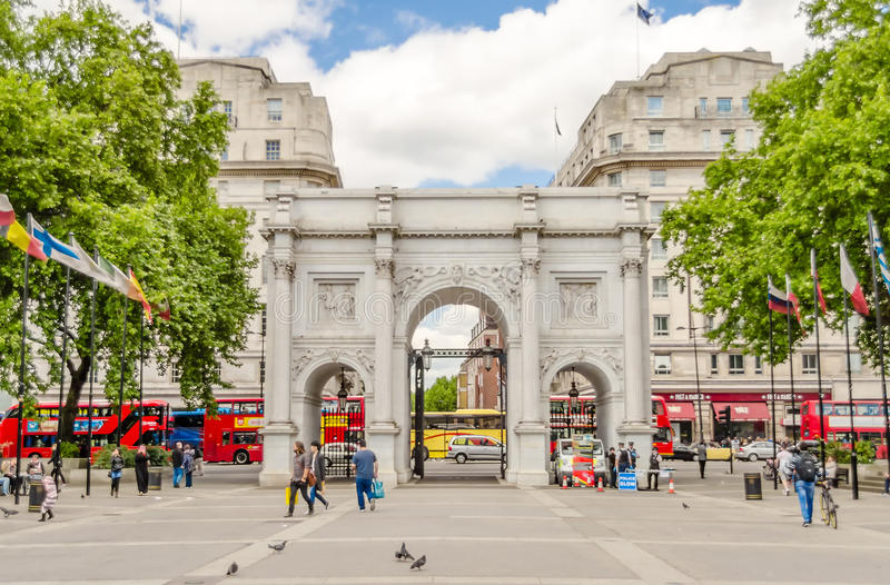 Marble Arch, London, UK. LONDON - MAY 30: People walking through Marble Arch on May 30, 2015 in London. The Arch was designed by J. Nash in 1827 to be the stock image