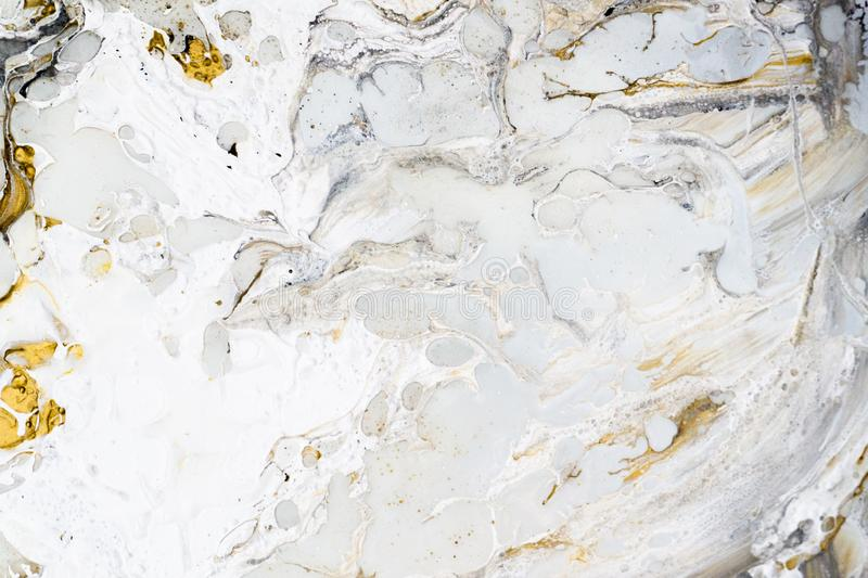 Marble background texture with gold, black, grey and white colors, using acrylic pouring medium art technique. Useful as a stock image