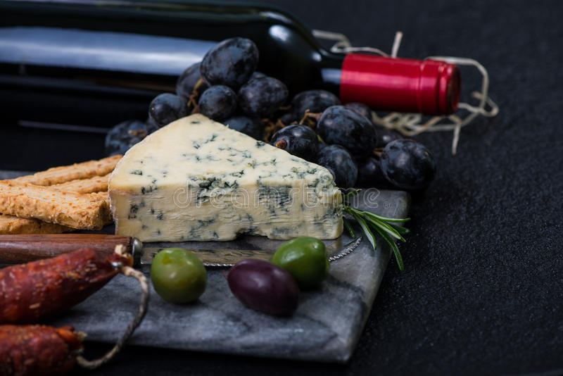 Marble board with cheese selection, wine and grapes. Marble board with cheese selection, red wine bottle and grapes on dark background from above, tapas and royalty free stock images