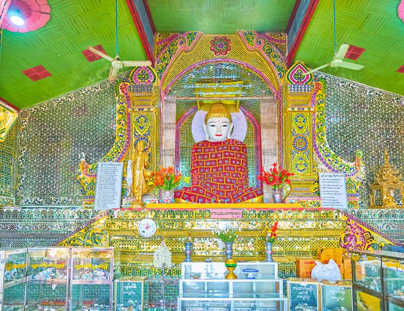 The marble Buddha in the shrine in Su Taung Pyae Pagoda, Mandala. MANDALAY, MYANMAR - FEBRUARY 23, 2018: The altar in The Su Taung Pyae Pagoda with marble stock photo