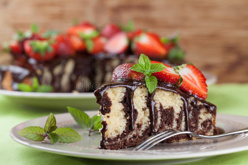 Marble cake with chocolate glaze and strawberries stock image