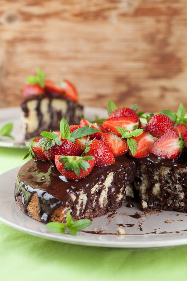 Marble cake with chocolate glaze and strawberries royalty free stock photography