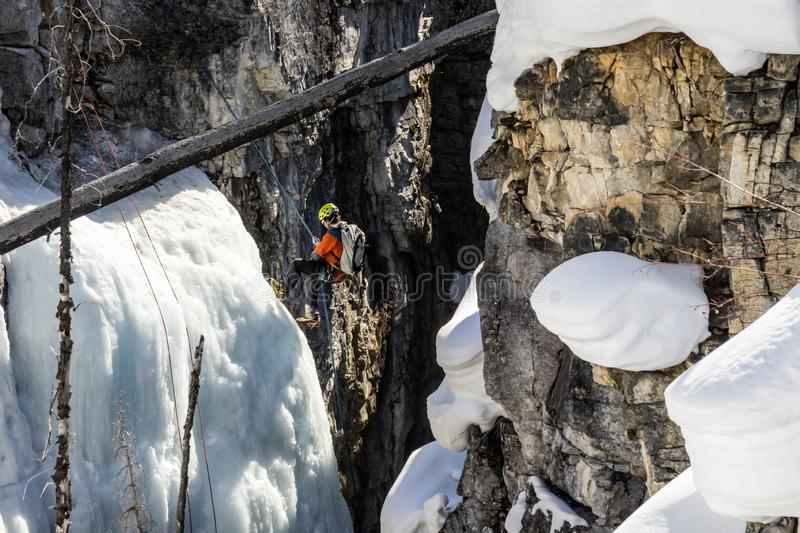 MARBLE CANYON, CANADA - MARCH 20, 2019: alpinists with backpacks preparing climbing down by ice to canyon royalty free stock image