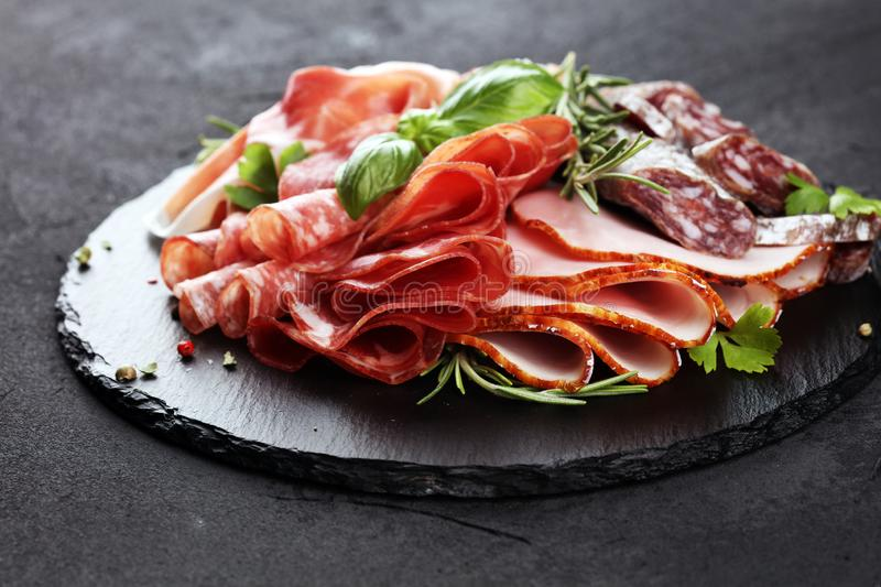 Marble cutting board with prosciutto, bacon, salami and sausages on wooden background. Rustic Meat platter. Marble cutting board with prosciutto, bacon, salami royalty free stock photography