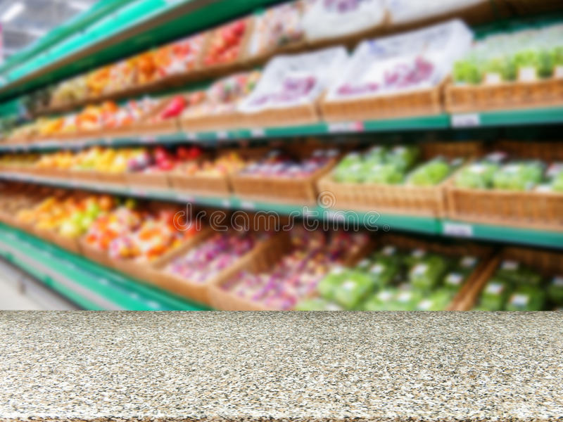 Marble empty table in front of blurred supermarket fruits shelf royalty free stock photo