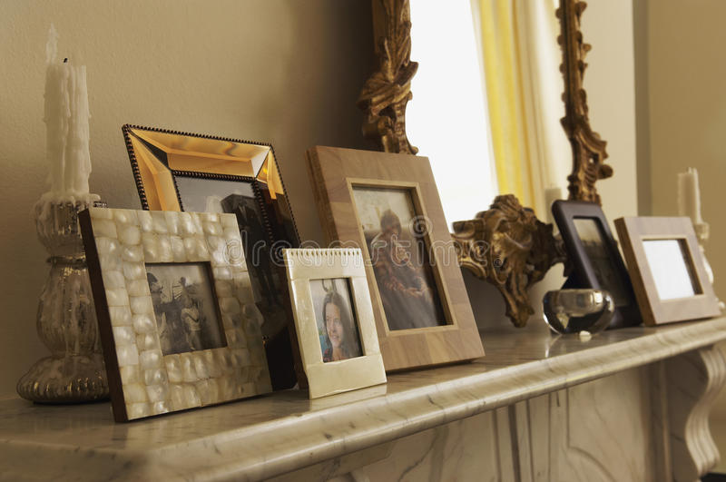 Marble Fireplace Mantel With Framed Pictures And Mirror. Closeup of marble fireplace mantel with framed pictures and mirror royalty free stock image