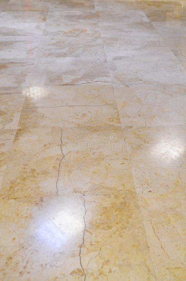 Marble floor tiles. Close up of brown and gold marble floor tiles with reflection of lights royalty free stock photography