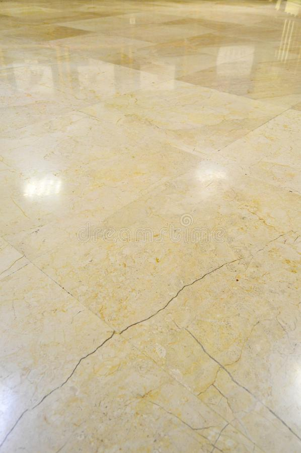 Marble floor tiles. Close up of brown and gold marble floor tiles with reflection of lights royalty free stock images
