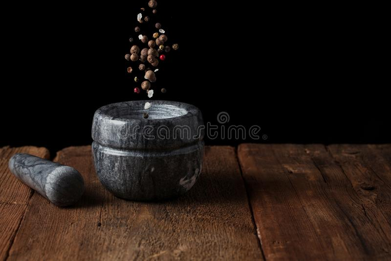 Marble mortar on old wooden table on black background with copy space. Pepper seeds fall into the mortar. freezer food.  royalty free stock photos