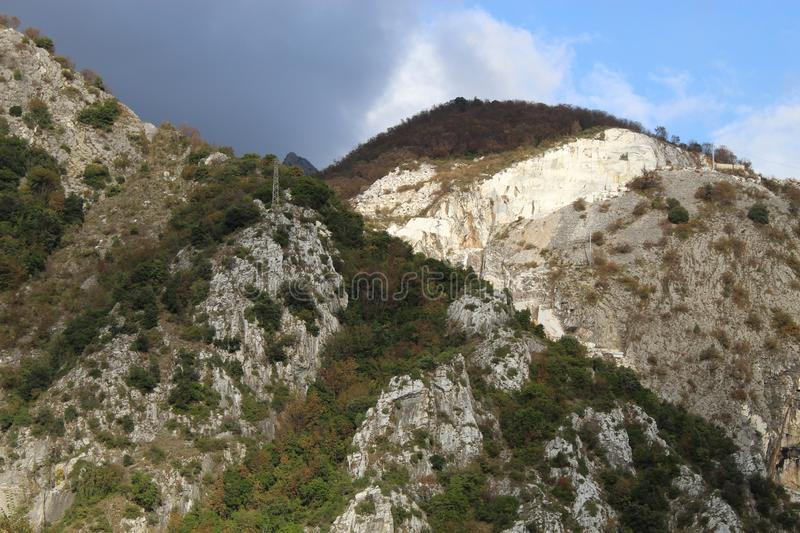 The Marble mountains in Italy. In the mountains the people get the marble. The mountains are very high and you can see also machines coming up there to get the royalty free stock photography