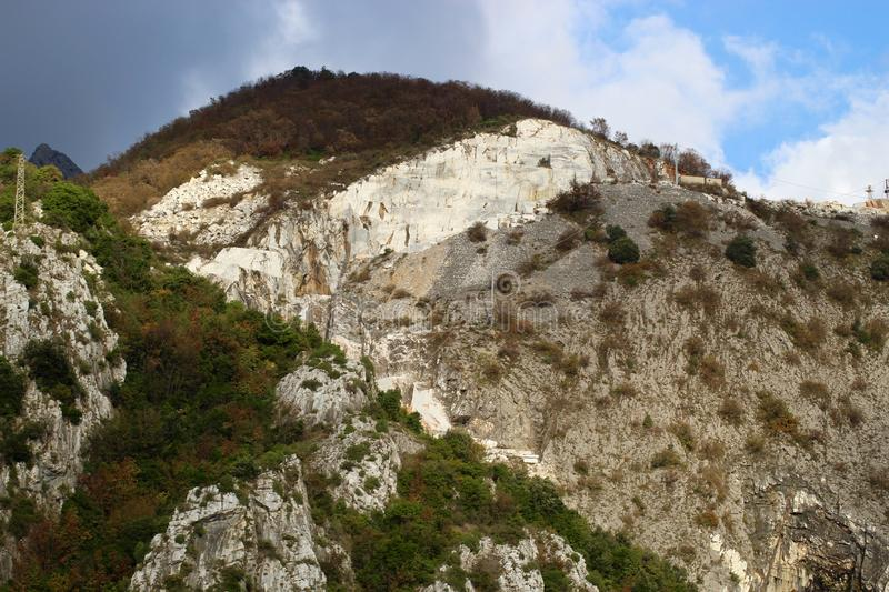 The marble mountains in Italy. The marble in the mountains. People working hard to get the marble to sell it over the whole world royalty free stock images