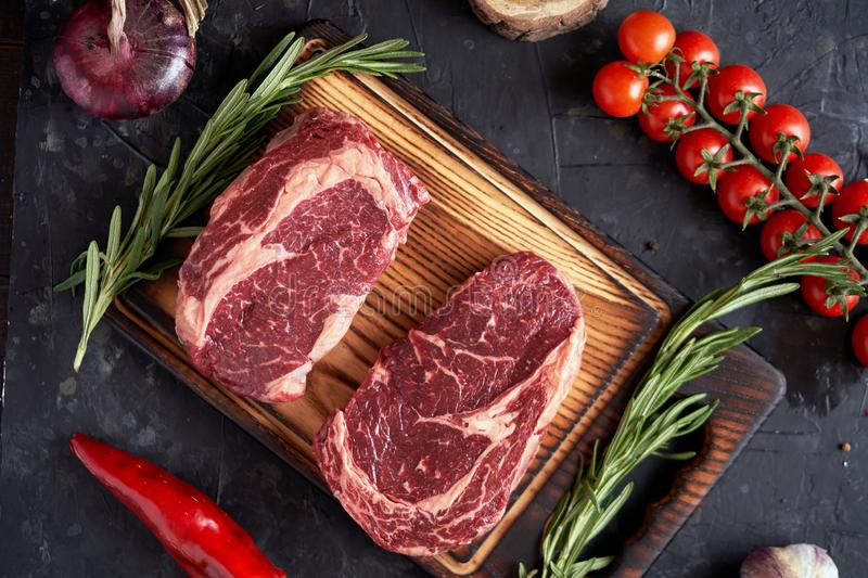 Marble ribeye steak on a cutting board with rosemary, peas, onions, garlic, red tomatoes on a branch on a concrete dark background royalty free stock photos