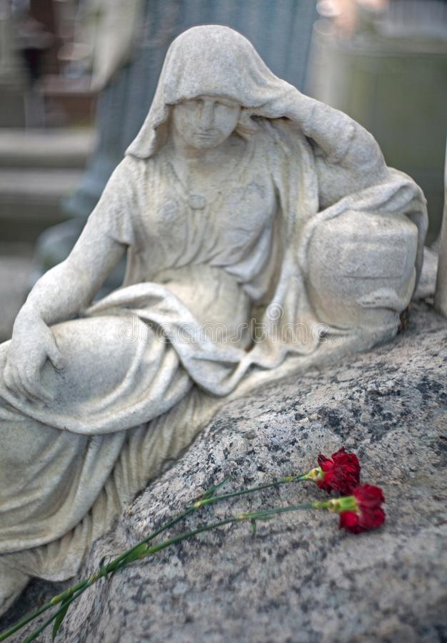 Marble sculpture of a grieving woman over a grave in with a two royalty free stock image