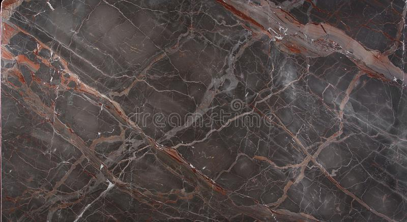 Marble slab brown with pink and red stripes is called Caravaggio. Natural stone, marble texture stock images