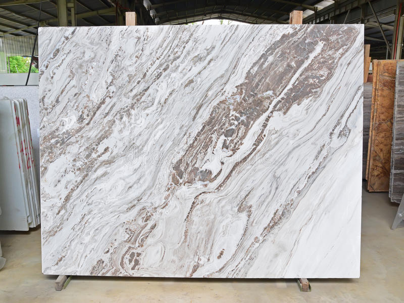 Marble slab supported by wooden frame on display in factory. Large Natural Marble slab with interesting pattern of dark brown veins supported by wooden frame on stock photography