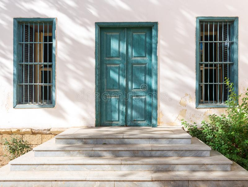Marble stair in front of white wall with green wooden old grunge door and two wrought iron windows stock image