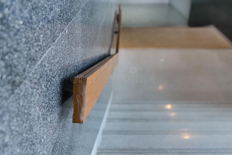 Marble stairs with wooden handrail in building for step up or down safety. Interior royalty free stock images