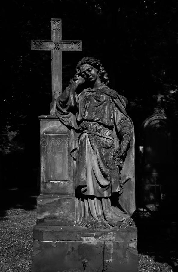 Marble statue angel with cross statue in Olsany Cemetery in Prague stock photography