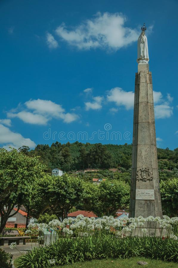 Statue of Our Lady over pillory in a flowered garden royalty free stock images