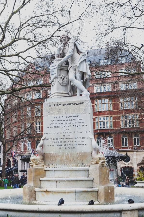 Marble statue of William Shakespeare at Leicester Square Garden in London, United Kingdom. London, UK - April 2018: The Shakespeare fountain and marble statue of stock photography