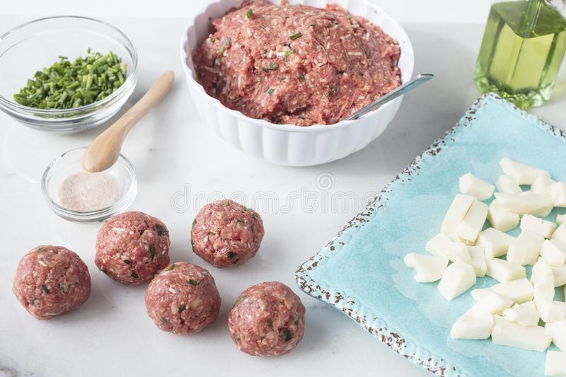 Marble table top with ingredients to make meatballs in stock image