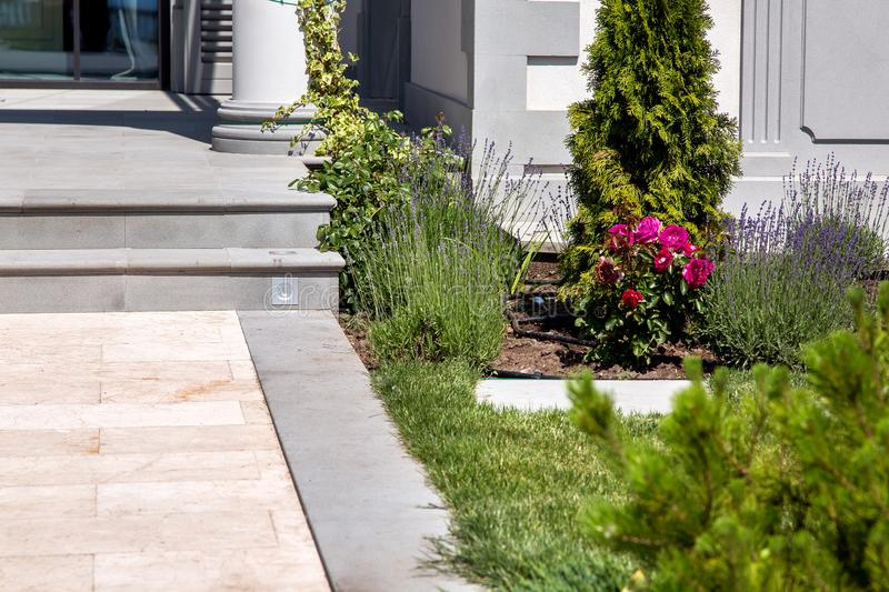 Marble walkway with flowerbed at the entrance to the house. stock images