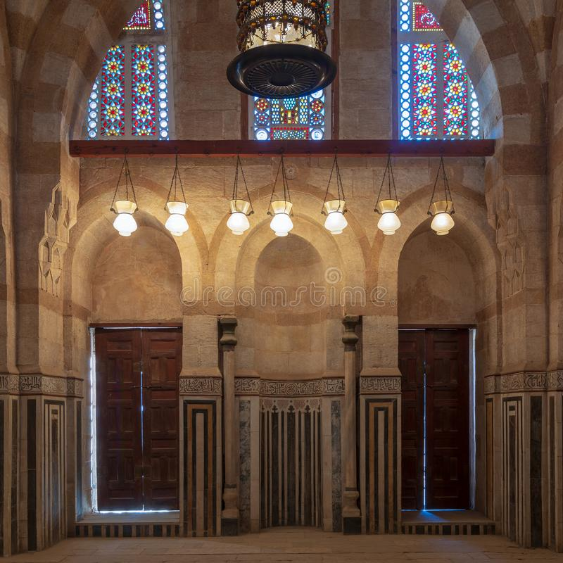 Marble wall with mihrab niche, wooden doors, huge arches and stained glass windows, Khayer Bek Mausoleum, Old Cairo, Egypt. Marble wall with mihrab niche, two stock images