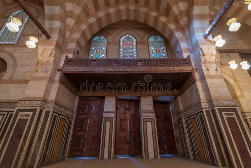 Marble wall with three wooden doors, huge arches and stained glass windows at Khayer Bek Mausoleum, Cairo, Egypt stock photography