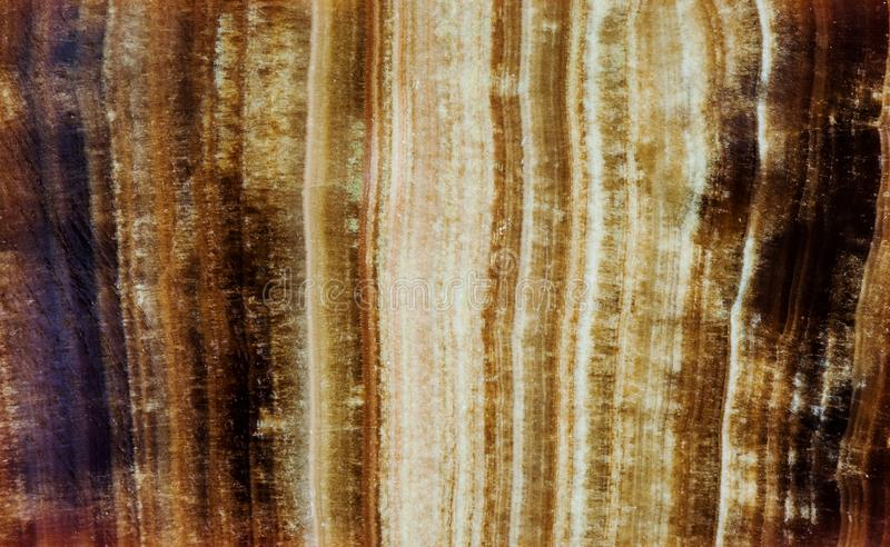 Marbled Onyx mineral stone pattern texture macro view. Beautiful brown color background layered chalcedony variety of royalty free stock photos