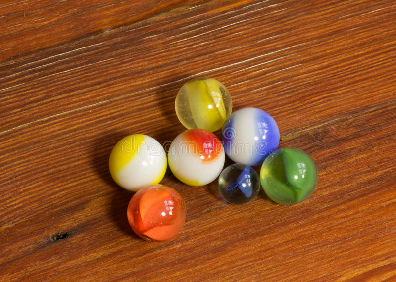 Marbles on Wood. Set of multicolored Marbles on a wooden floor royalty free stock image