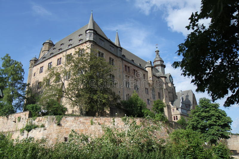 Marburg Castle. In Germany on a clear day with clouds and a view of the towers, walls, clock and surrounding trees royalty free stock photo