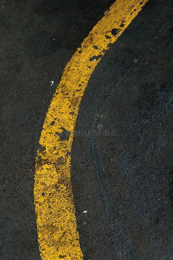 Marcações de estrada listradas amarelas no asfalto preto fotos de stock