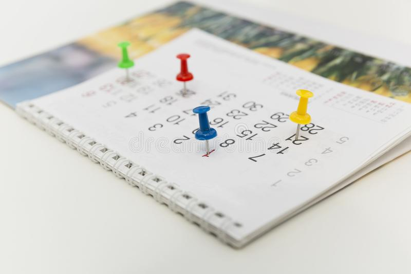 Marca colorida del empuje de los pernos en un calendario Horario ocupado imagenes de archivo